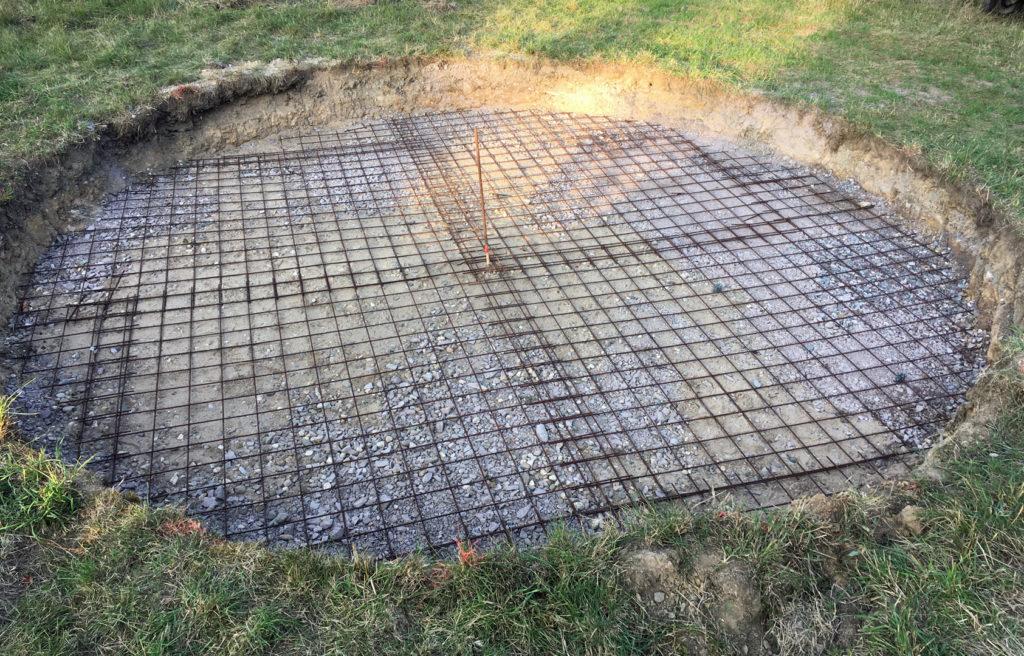 Runde Grube in einer Wiese, die mit Baustahlmatten ausgelegt ist.
